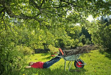 Man lying on grass with legs on wheelbarrow - FOLF07811