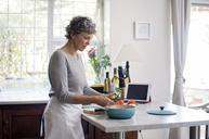 Mature woman chopping vegetables in kitchen - CAVF33566