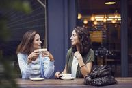 Female friends talking while having coffee at sidewalk cafe - CAVF33581