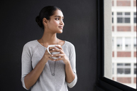 Smiling female interior designer holding coffee mug while looking through window in office - CAVF33617