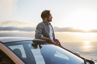 Young man looking away while standing outside car by sea during sunset - CAVF33635