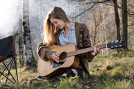 Beautiful woman playing guitar in forest - CAVF33683