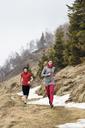 Athletes running on mountain during winter - CAVF33692