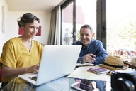 Happy senior couple using laptop while planning vacation at home - CAVF33743