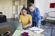 Happy senior couple using laptop while planning vacation at home - CAVF33749