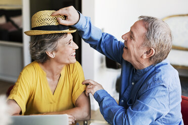Happy senior man putting sunhat on mature woman while planning vacation at home - CAVF33755