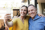Cheerful senior couple taking selfie through smart phone at porch - CAVF33761