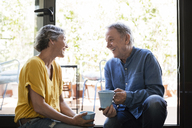 Cheerful senior couple talking while holding coffee mugs by window at home - CAVF33767