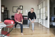 Happy senior couple doing stretching exercise at home - CAVF33782
