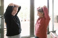 Cheerful senior couple exercising by window at home - CAVF33785
