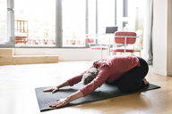 Mature woman practicing yoga in child's pose at home - CAVF33791
