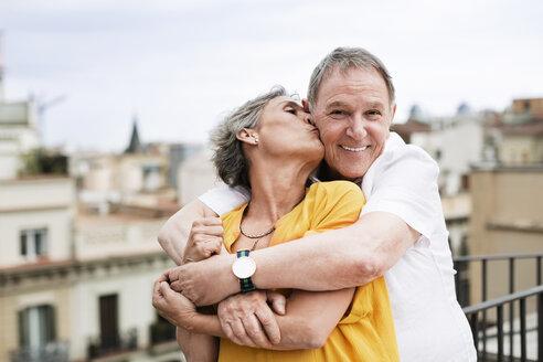 Romantic mature woman kissing senior man on terrace - CAVF33812