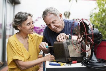 Senior couple repairing old-fashioned radio at yard - CAVF33827