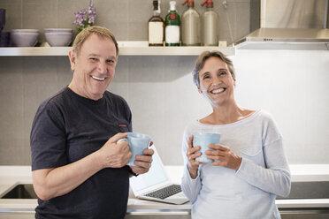 Portrait of happy senior couple holding coffee mugs in kitchen - CAVF33836