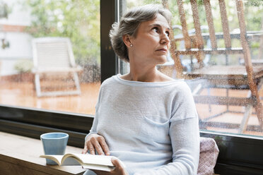 Thoughtful mature woman looking through window while holding book at home - CAVF33839