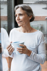 Thoughtful mature woman holding coffee mug while looking through window at home - CAVF33842