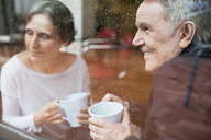 Happy senior couple looking through window at home - CAVF33845