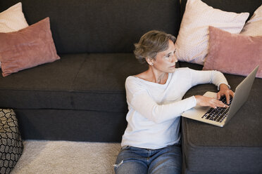 Mature woman using laptop while sitting on floor in living room - CAVF33848