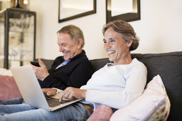 Cheerful senior couple using laptop and smart phone on sofa at home - CAVF33851