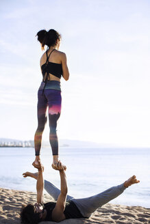 Couple performing yoga on shore against sky - CAVF33866
