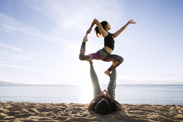 Couple doing yoga on beach against sky - CAVF33869