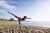 Determined woman performing yoga in Warrior 3 pose on beach - CAVF33872