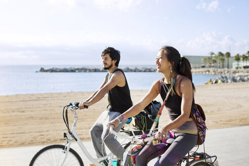 Sporty couple riding bicycles on road by beach - CAVF33878