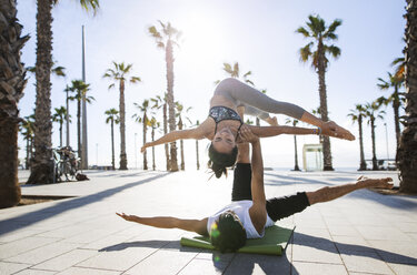 Man lifting woman while doing yoga on footpath by beach - CAVF33881