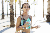 Portrait of happy sporty woman holding water bottle on footpath during summer - CAVF33887