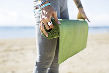 Midsection of woman holding rolled up exercise mat on beach - CAVF33893