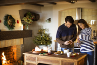 Smiling couple decorating home during Christmas - CAVF33932