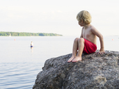 Boy sitting on rock at seaside - FOLF08058
