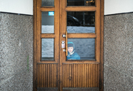 Boy looking through entrance door - FOLF08064