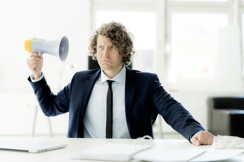 Businessman sitting in office trying out megaphone - HHLMF00158