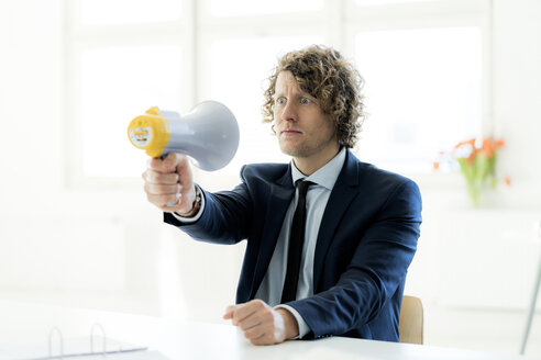 Businessman sitting in office trying out megaphone - HHLMF00161