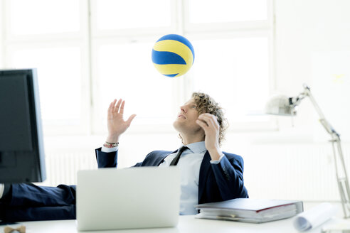 Businessman playing with a ball in his office - HHLMF00167