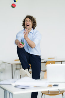 Laughing businessman juggling balls in his office - HHLMF00212