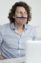 Businessman balancing pencil on his face - HHLMF00227