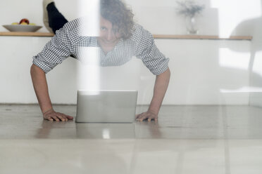 Businessman working from home with his laptop, while doing a plank - HHLMF00233