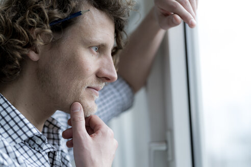Portrait of a smiling man, looking out of window - HHLMF00236