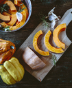 Pumpkin slices, garlic and rosemary on wooden board and in casserolle - GIOF03897