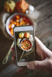 Taking photo of casserolle of pumpkin dish with smartphone - GIOF03903