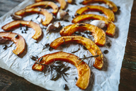 Baked slices of pumpkin, garlic and rosemary on baking paper - GIOF03909