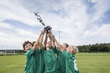 Young football players cheering with cup - WESTF24034