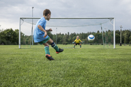 Young football player kicking ball in front of goal with goalkeeper - WESTF24040