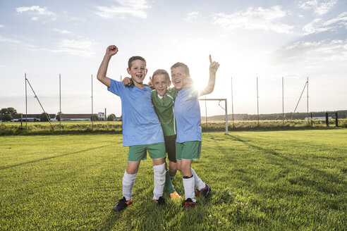 Young football players cheering on football ground - WESTF24043