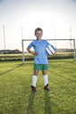 Portrait of smiling young football player holding ball on football ground - WESTF24046