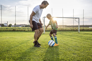 Coach and young football player on football ground at sunset - WESTF24061