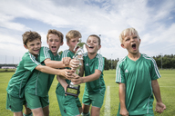 Germany, young football players cheering with cup - WEST24065