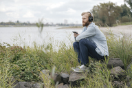 Germany, Duesseldorf, man listening music with headphones and smartphone in nature - KNSF03665